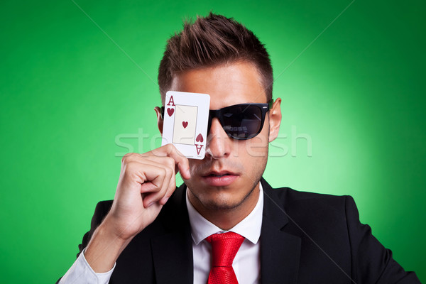 business man covers one eye with an ace of hearts Stock photo © feedough