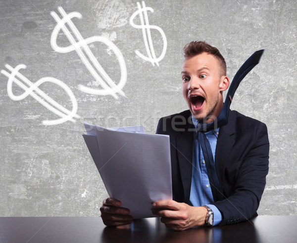 Stock photo: surprised businessman reading shocking good results
