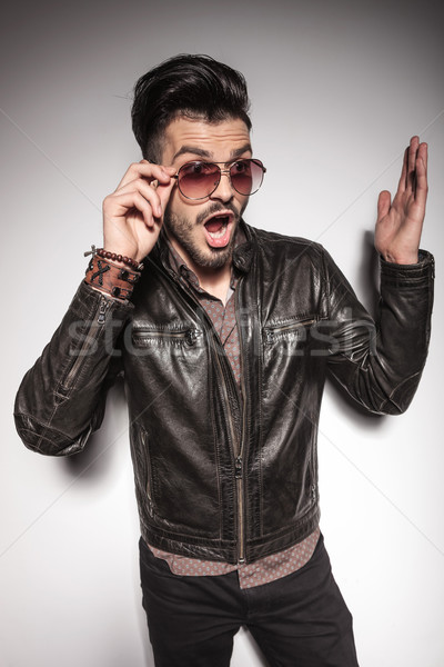 Amazed young fashion man fixing his sunglasses  Stock photo © feedough