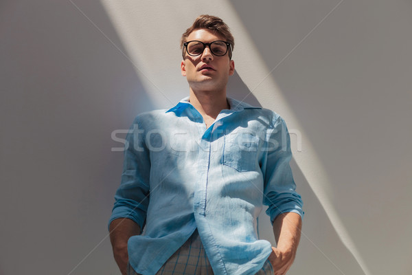 Attractive casual man leaning on a wall  Stock photo © feedough