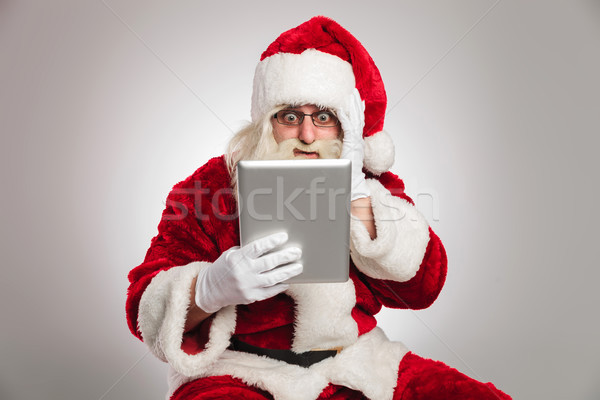santa claus is reading something shocking on his tablet  Stock photo © feedough