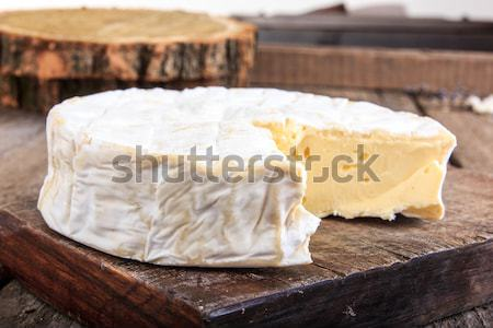 Closeup of round cheese on a wooden board Stock photo © feelphotoart
