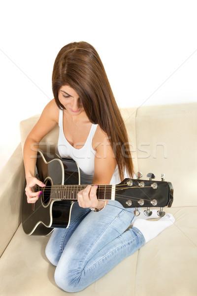 Lány játszik gitár kanapé aranyos barna hajú Stock fotó © feelphotoart