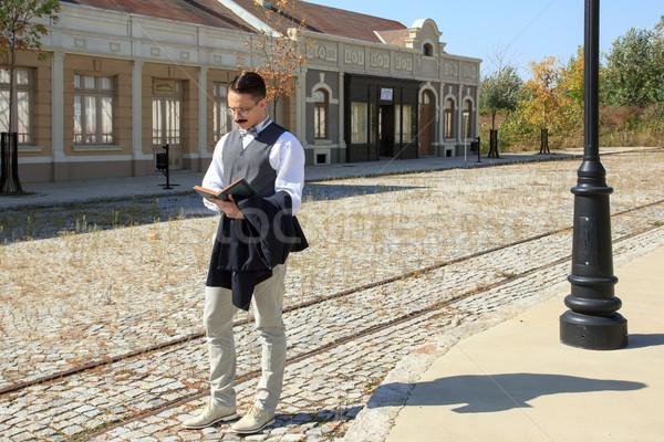 Man with mustache walking along the rails reading book Stock photo © feelphotoart