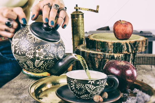 Pouring tea from teapot on old retro wooden table Stock photo © feelphotoart