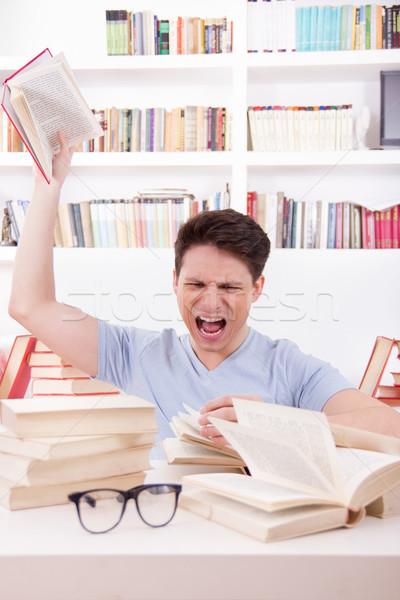 angry student  surrounded by books  throws a book Stock photo © feelphotoart
