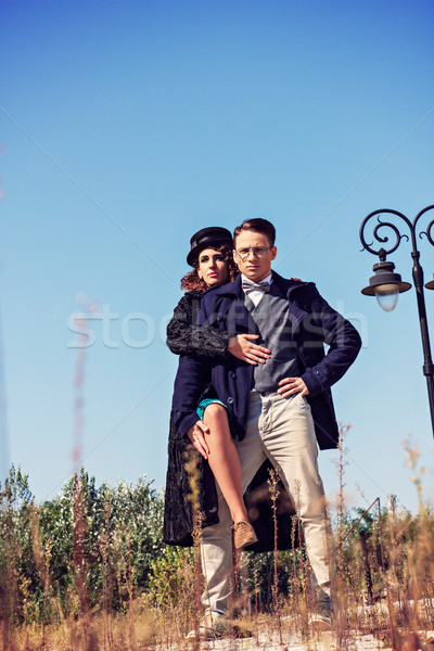 Two fashion people in vintage style posing in below shot Stock photo © feelphotoart