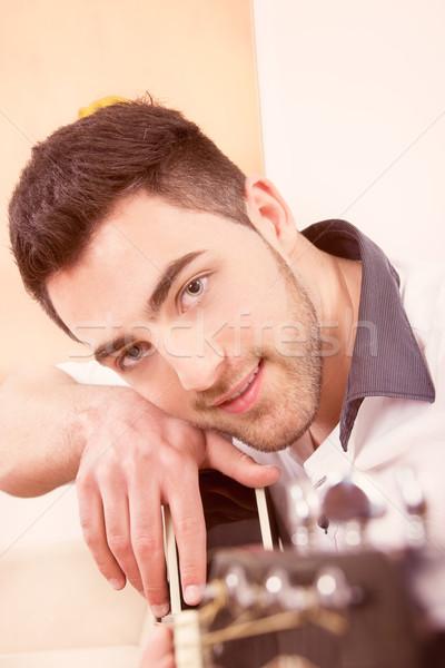 Férfi dől gitár mosolyog jóképű férfi kék szemek Stock fotó © feelphotoart