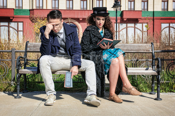 Stock photo: Young retro couple in quarrel sitting on bench reading book