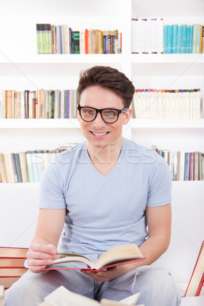 smiling man with glasses reading a book on the couch Stock photo © feelphotoart