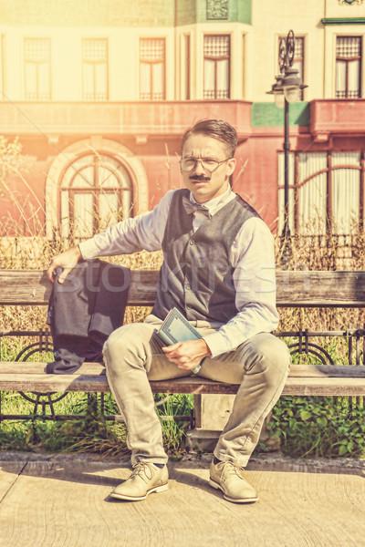 Férfi öltöny szemüveg bajusz tart könyv Stock fotó © feelphotoart