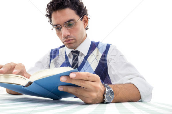adult serious man in pullover with glasses sitting and reads boo Stock photo © feelphotoart