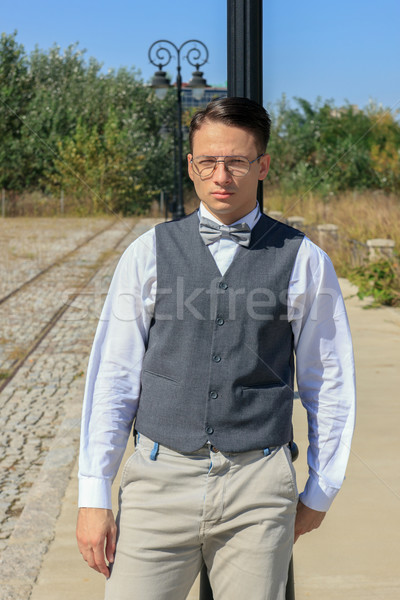man in shirt and vest with bow tie and glasses, standing leaning Stock photo © feelphotoart
