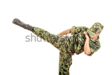 soldier in a green camouflage uniform kicking Stock photo © feelphotoart