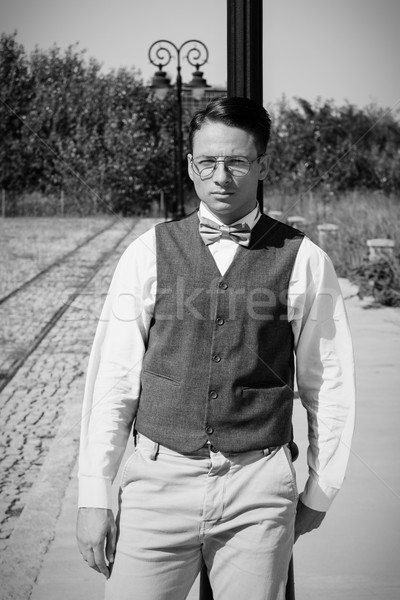 Man in vest standing by the railway leaning against lamppost Stock photo © feelphotoart