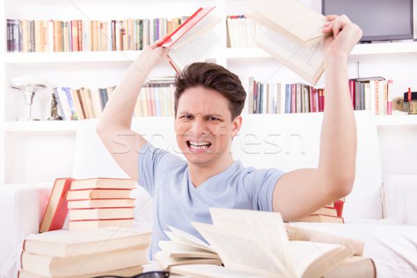 angry student  surrounded by books  throws books Stock photo © feelphotoart