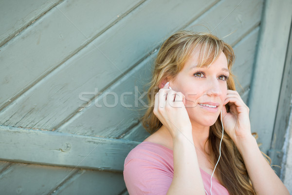 Outdoor Portrait of Young Adult Brown Eyed Woman Listening To Mu Stock photo © feverpitch