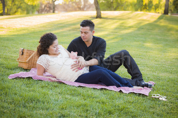 Pregnant Hispanic Couple with Piggy Bank on Belly in Park Stock photo © feverpitch