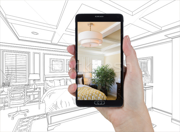 Hand Holding Smart Phone Displaying Photo of Bedroom Drawing Beh Stock photo © feverpitch