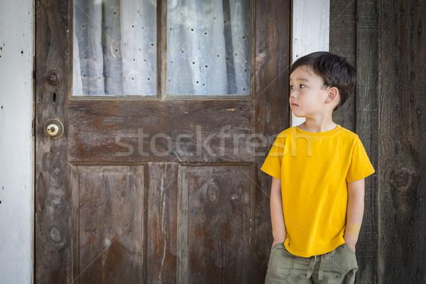Melancholy Mixed Race Boy Standing In Front of Door Stock photo © feverpitch
