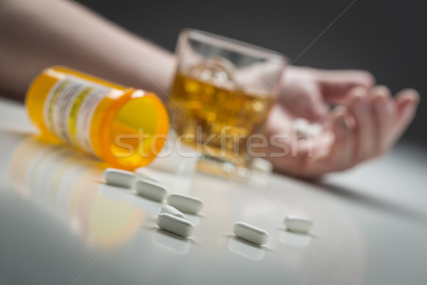 Hand on Ground Behind Scattered Drugs and Glass of Alcohol Stock photo © feverpitch