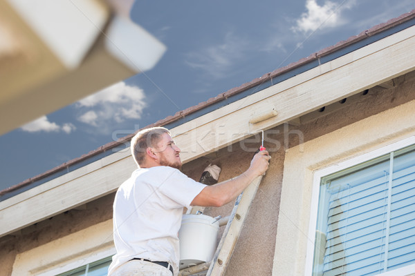 Professional Painter Using Small Roller to Paint House Fascia Stock photo © feverpitch