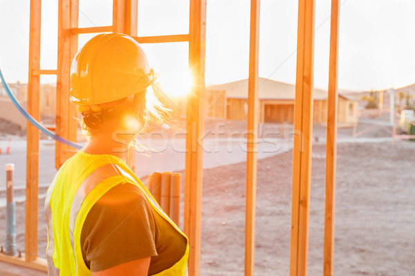 Female Construcion Worker Looking Out From New Home Framing Stock photo © feverpitch