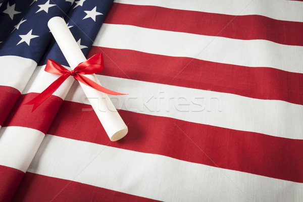Ribbon Wrapped Diploma Resting on American Flag with Copy Space Stock photo © feverpitch