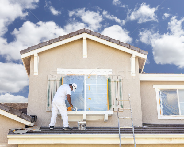 House Painter Painting the Trim And Shutters of Home Stock photo © feverpitch