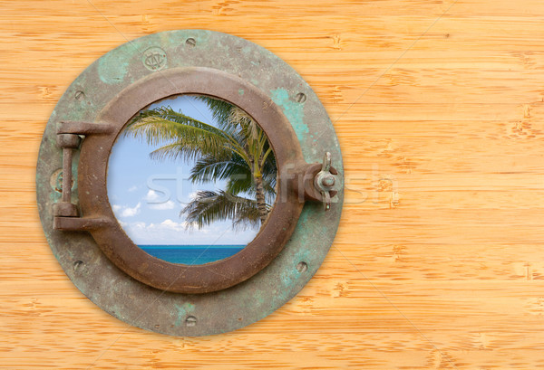 Antique Porthole with Tropical Beach View on Bamboo Wall Stock photo © feverpitch
