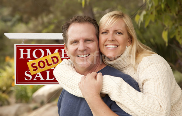 Happy Couple in Front of Sold Real Estate Sign Stock photo © feverpitch