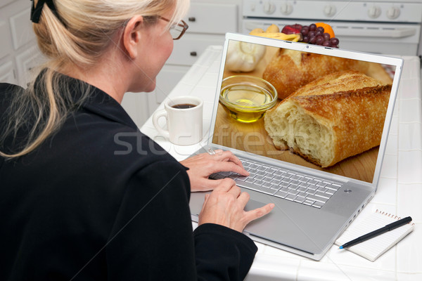 Stock photo: Woman In Kitchen Using Laptop - Food and Recipes