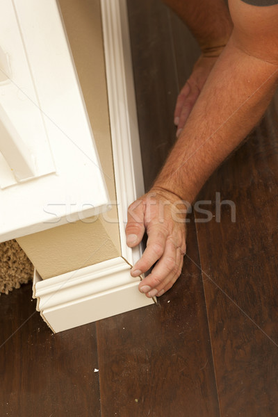 Contractor Fitting New Baseboard to Wall and New Laminate Floori Stock photo © feverpitch