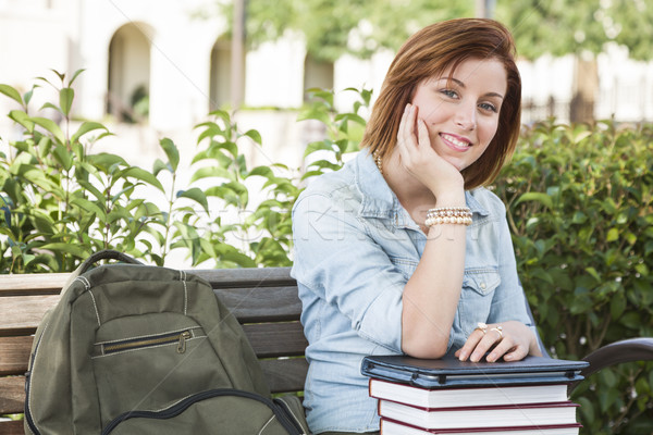 Young Female Student Sitting On Campus with Backpack and Books Stock photo © feverpitch
