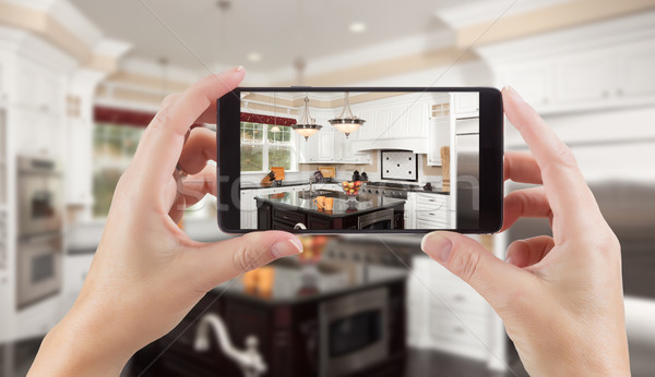 Female Hands Holding Smart Phone Displaying Photo of Kitchen Beh Stock photo © feverpitch