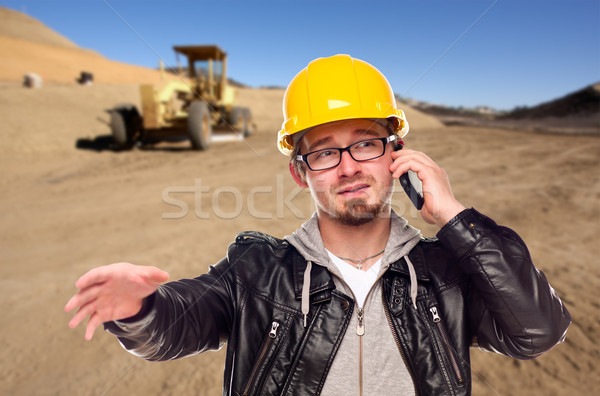 Young Cunstruction Worker on Cell Phone in Dirt Field with Tract Stock photo © feverpitch