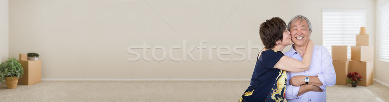 Stock photo: Happy Chinese Couple Kissing in Empty Room with Moving Boxes Ban