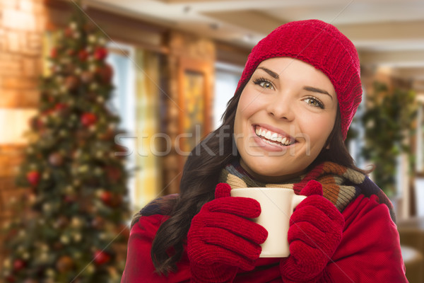 Stock photo: Mixed Race Woman Wearing Hat and Gloves In Christmas Setting