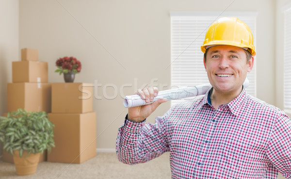 Male Construction Worker In Room With Boxes Holding Roll of Blue Stock photo © feverpitch
