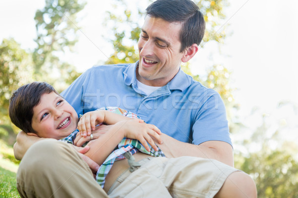 Loving Young Father Tickling Son in the Park. Stock photo © feverpitch
