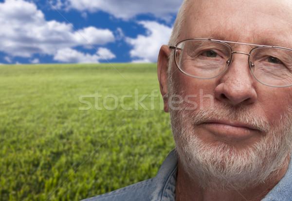 Melancolia senior homem campo de grama atrás nuvens Foto stock © feverpitch