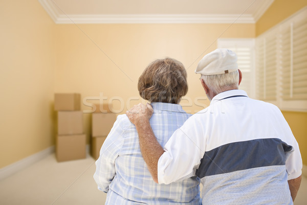 Senior Couple In Room Looking at Moving Boxes on Floor Stock photo © feverpitch