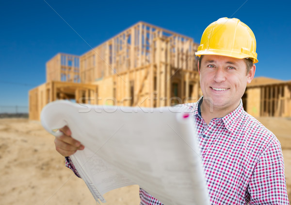 Smiling Contractor Wearing Hardhat Holding Blueprints at Home Co Stock photo © feverpitch