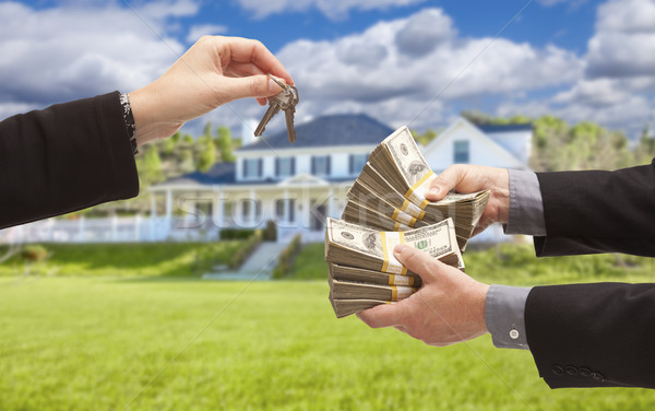 Mand Handing Woman Cash for Keys in Front of House Stock photo © feverpitch