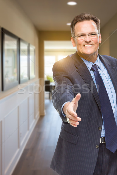 Male Agent Reaching for Hand Shake in Hallway of House Stock photo © feverpitch