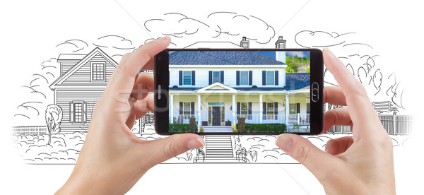 Hands Holding Smart Phone Displaying Home Photo of Drawing Behin Stock photo © feverpitch