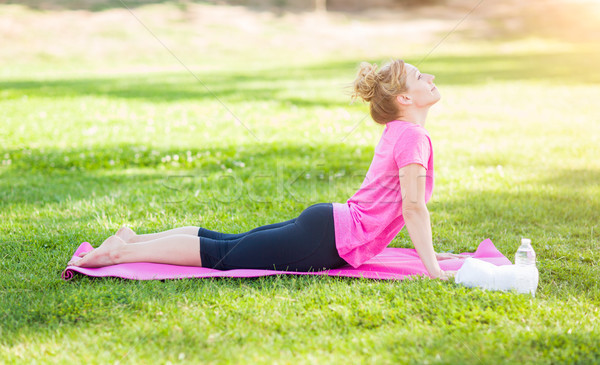 Young Fit Adult Woman Outdoors on The Grass Doing the Upward Dog Stock photo © feverpitch
