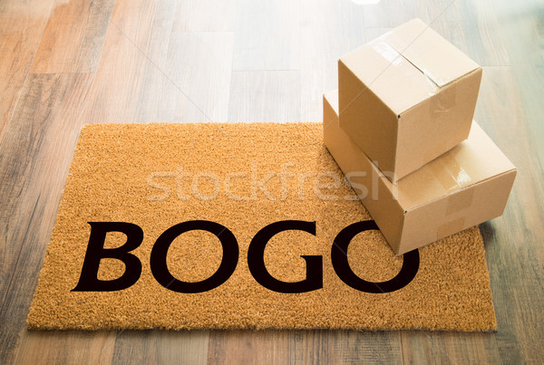 BOGO Welcome Mat On Wood Floor With Shipment of Boxes Stock photo © feverpitch