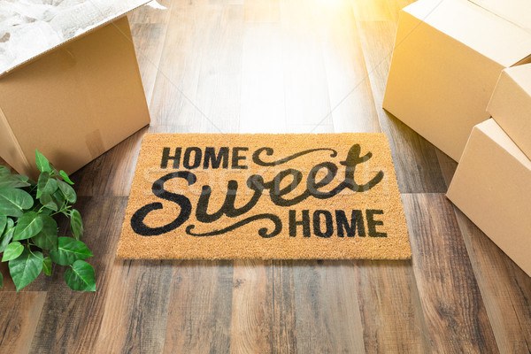 Home Sweet Home Welcome Mat, Moving Boxes and Plant on Hard Wood Stock photo © feverpitch