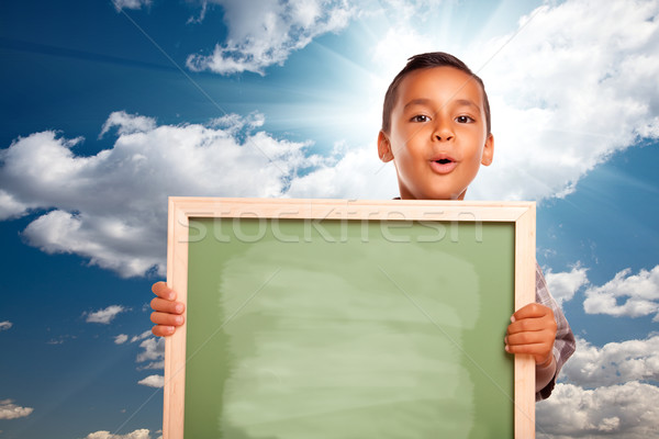 Proud Hispanic Boy Holding Blank Chalkboard Over Sky Stock photo © feverpitch